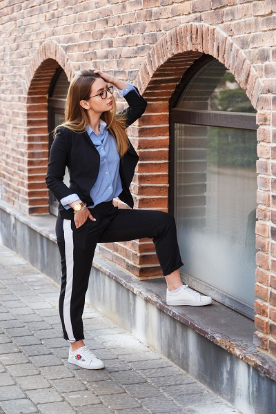 Fashionable Russian girl's look with a black jacket and blue blouse near a brick wall
