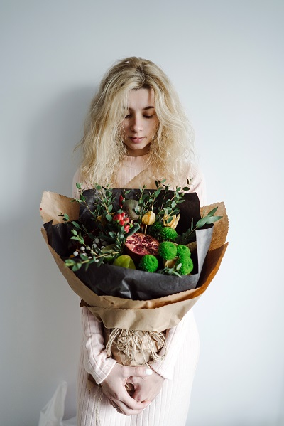 Young blond Russian woman posing with a huge bouquet of flowers in front of a camera