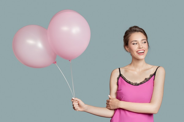 Portrait of a young smiling Russian girl holding pink balloons while looking sideways