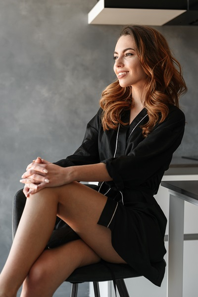 Smiling young attractive Russian female sitting on a chair with her arms crossed together