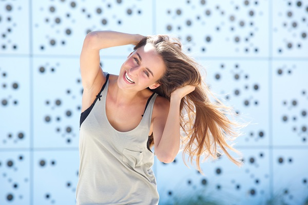 Young smiling Russian woman laughing with a hand in her hair posing for the camera