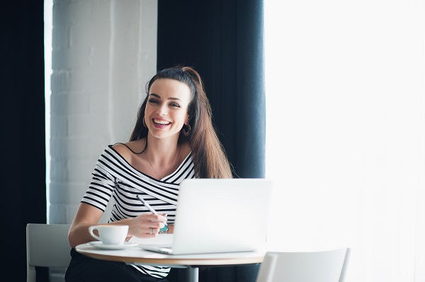 Portrait of Russian woman laughing and looking away with a laptop in a cafe
