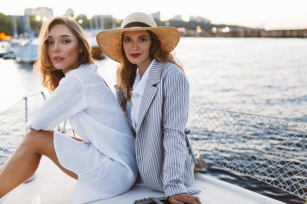 Young beautiful Russian women sitting near water while posing for the camera