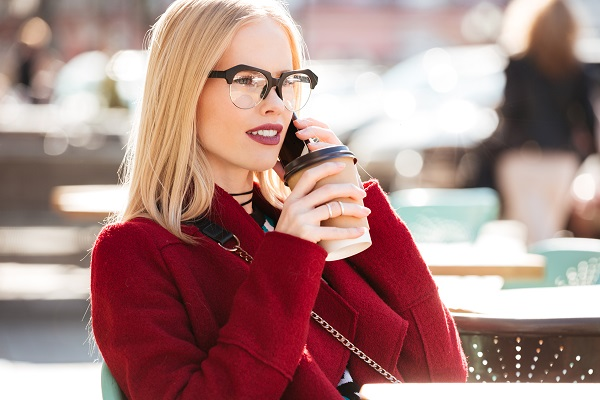 Amazing young blonde Russian woman talking by phone drinking her cup of fresh coffee
