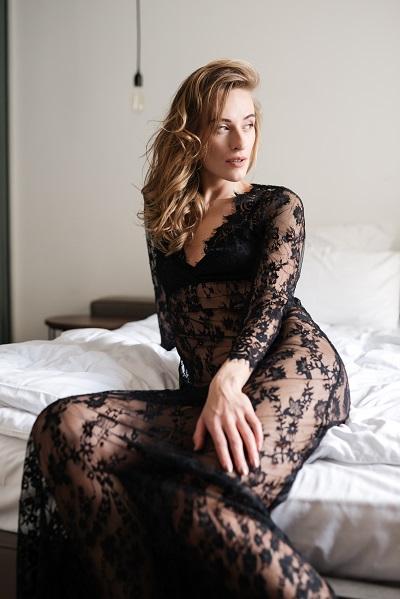 Amazing brunette Russian woman sitting indoors dressed in sexy black lingerie looking sideways