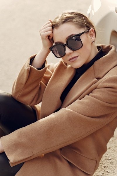 Elegant charming Russian woman in a brown coat wearing fashionable sunglasses in a spring city