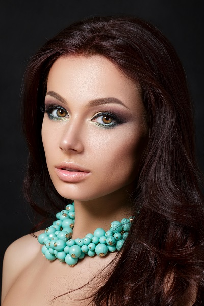 Portrait of a young beautiful Russian woman wearing a blue necklace dreamily looking in the camera