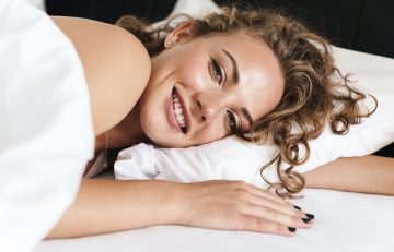 Close up of a beautiful young blonde haired Russian woman lying on a white pillow in her bed